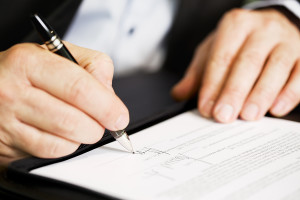Businessman sitting at office desk signing a contract with shall