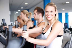 Row of young adults exercising on elliptical machines. Horizontal shot.